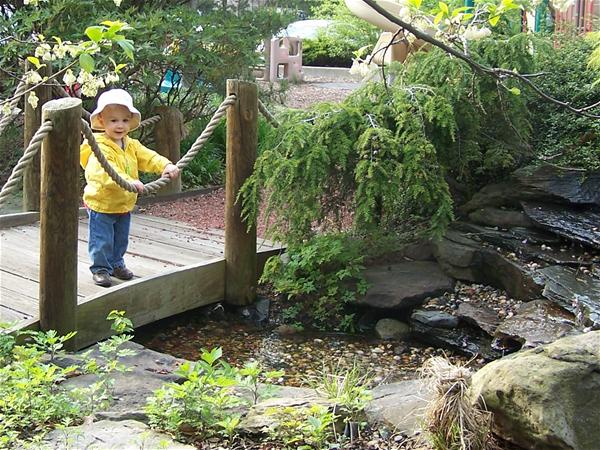 Child on a wooden bridge over a creek