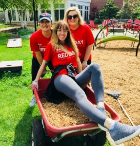 Three volunteers posing with a wheelbarrow full of mulch at the Cleveland House