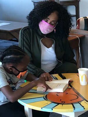 Rabia and Cameron Harris wearing masks and reading together